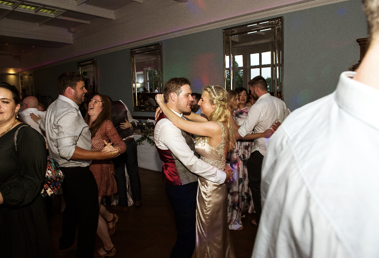 Wedded couple dance with guests