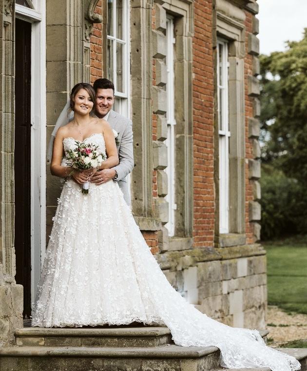 Bride's dress flows on venue steps