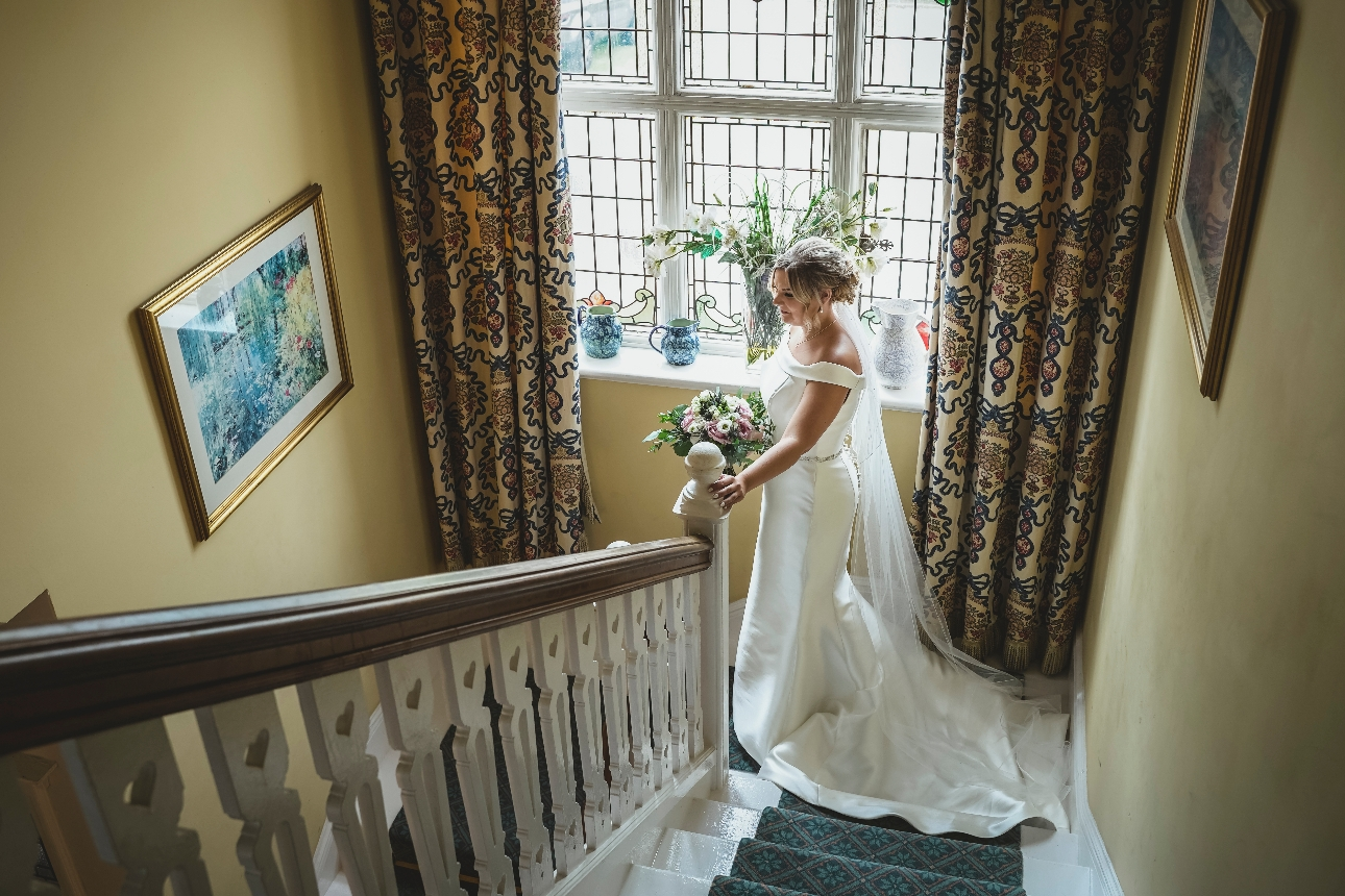 Bride walking down stairs with bouquet