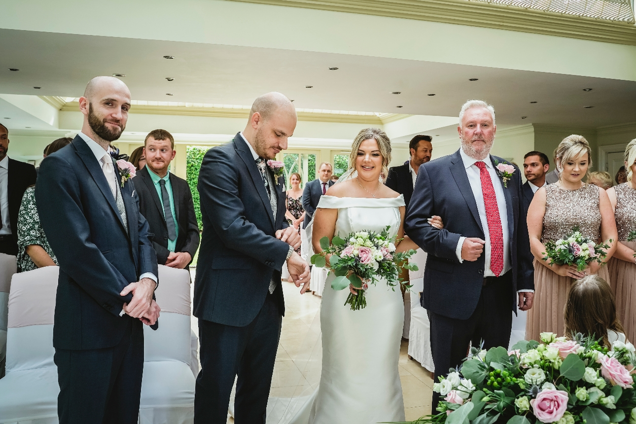 Groom checks watch at end of the aisle