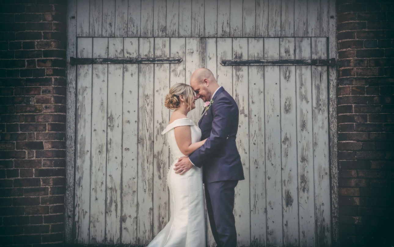Couple pose infront of barn doors